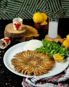 Gebakken sprotjes in ronde vorm geserveerd met peterselie en citroen