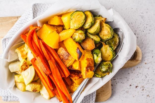 Gebakken spruitjes, courgette, pompoen en wortelen op een witte schotel. gezond veganistisch voedselconcept.