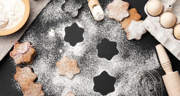 Gebakken stervormig peperkoekkoekje bestrooid met poedersuiker op een zwarte tafel en ingrediënten