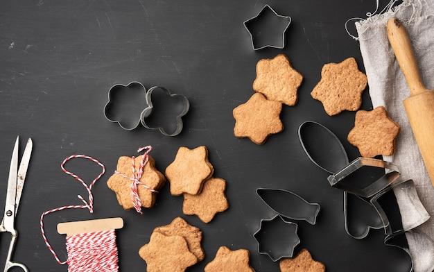 Gebakken stervormige peperkoekkoekjes, houten deegroller en metalen uitstekers op een zwarte tafel, bovenaanzicht