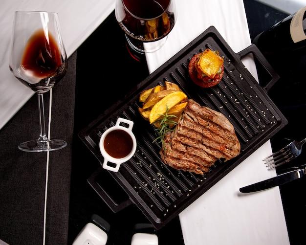 Gebakken stuk biefstuk met aardappelen thuis en een glas wijn