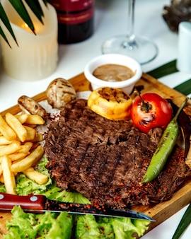 Gebakken stuk vlees met friet en groenten