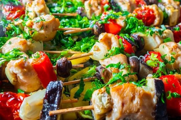 Gebakken stukjes kip en groenten aan spiesjes