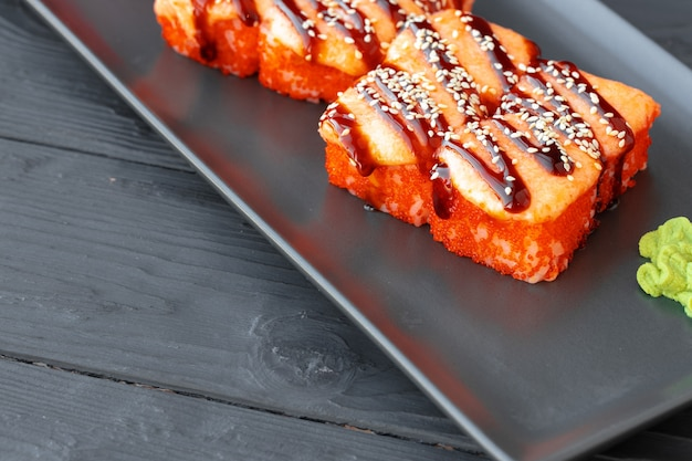 Gebakken sushibroodje dat op zwarte plaat op houten lijst wordt gediend