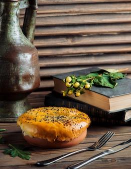 Gebakken taart gevuld met voedsel in een aardewerken schaal