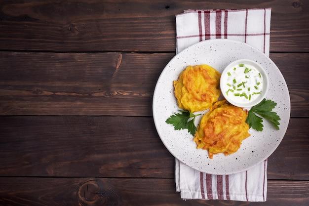 Gebakken taarten van geraspte aardappelen met saus.