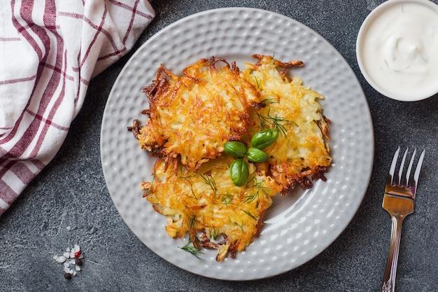 Gebakken taarten van geraspte aardappelen op het bord met saus, traditionele pannenkoeken boxty raggmunk