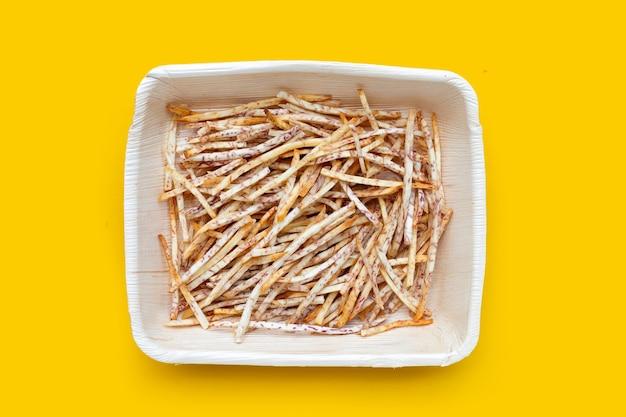 Gebakken taro sticks in plaat op gele achtergrond.