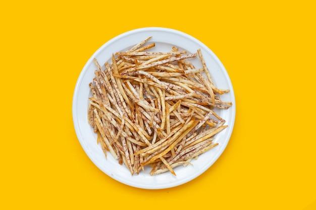 Gebakken taro sticks in witte plaat op gele achtergrond.