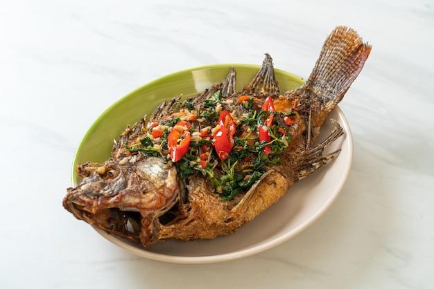 Gebakken tilapia-vis met basilicum-chili-knoflooksaus erop