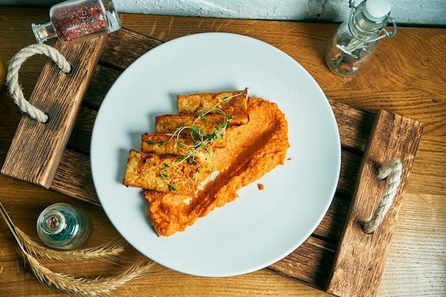 Gebakken tofu met oranje smoothie op een witte plaat op een houten bord. bovenaanzicht plat voedsel. vegetarische gezonde maaltijd