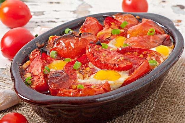 Gebakken tomaten met knoflook en eieren versierd met groene uien