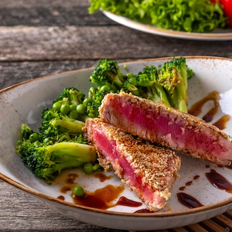 Gebakken tonijn met groenten op een bord in rustieke stijl