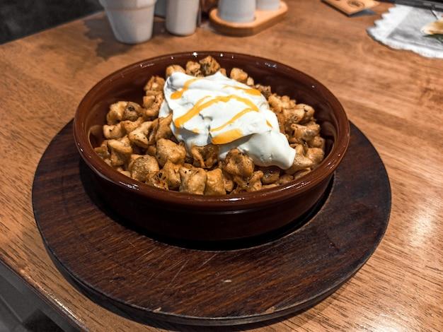 Gebakken turkse manti met kruiden en room in een traditioneel gerecht op een houten dienblad. selectieve aandacht. klein focusgebied