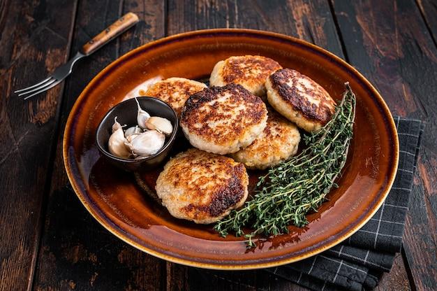 Gebakken varkens- en rundvleeskoteletten of pasteitjes in een rustieke plaat. donkere houten achtergrond. bovenaanzicht.