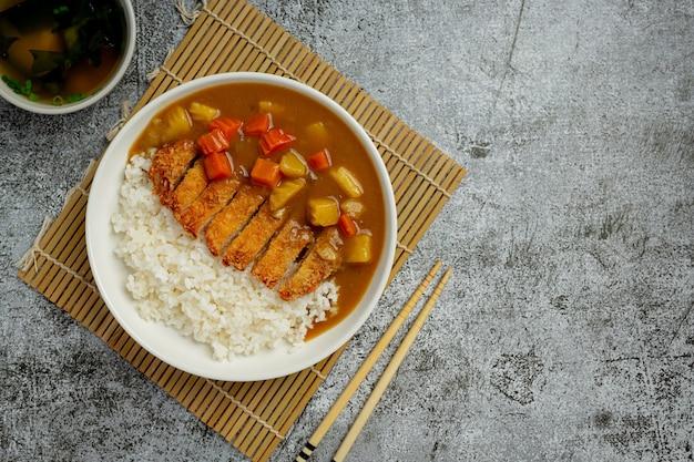 Gebakken varkenskotelet curry met rijst op een donkere ondergrond