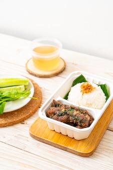 Gebakken varkensribbetjes met saus en rijst in leveringsdoos