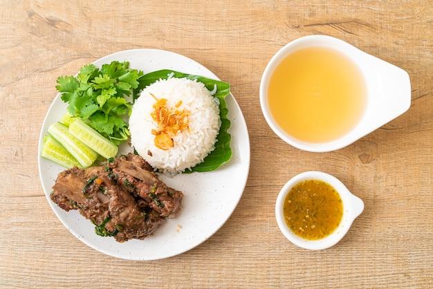 Gebakken varkensribbetjes met saus en rijst