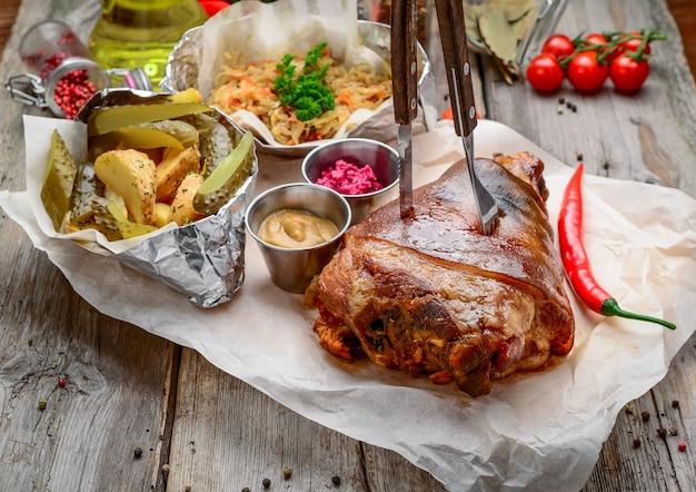 Gebakken varkensvlees been met aardappelen op houten bord