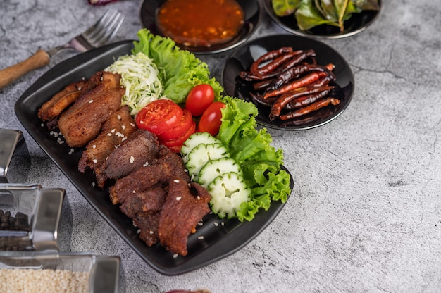 Gebakken varkensvlees gegarneerd met sesam in een zwarte schotel.