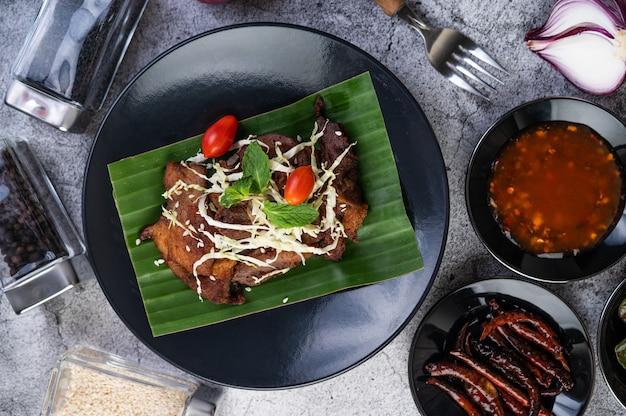 Gebakken varkensvlees gegarneerd met sesamzaadjes op een bananenblad in een zwarte schotel.
