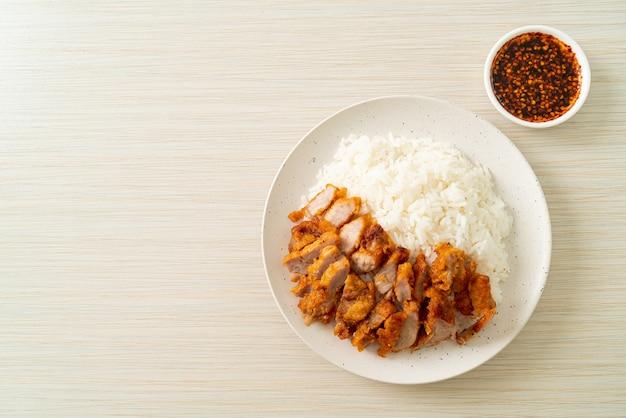 Gebakken varkensvlees gegarneerd op rijst met pittige dipsaus