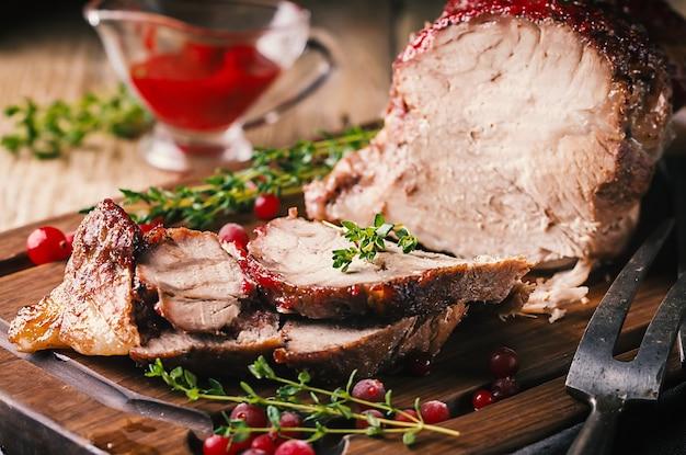 Gebakken varkensvlees met amerikaanse veenbessaus en tijm over houten oppervlakteconcepten vakantievoedsel
