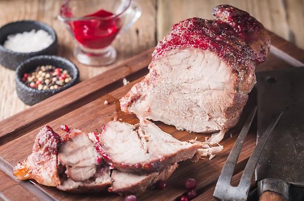 Gebakken varkensvlees met amerikaanse veenbessensaus en tijm over houten. concepten vakantievoedsel.