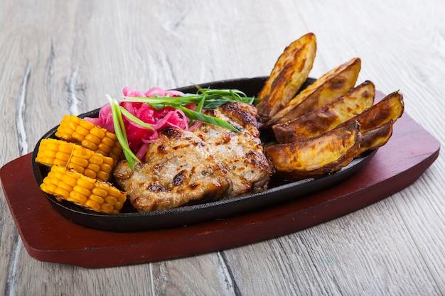 Gebakken varkensvlees met gebakken aardappelen en maïs in een pan