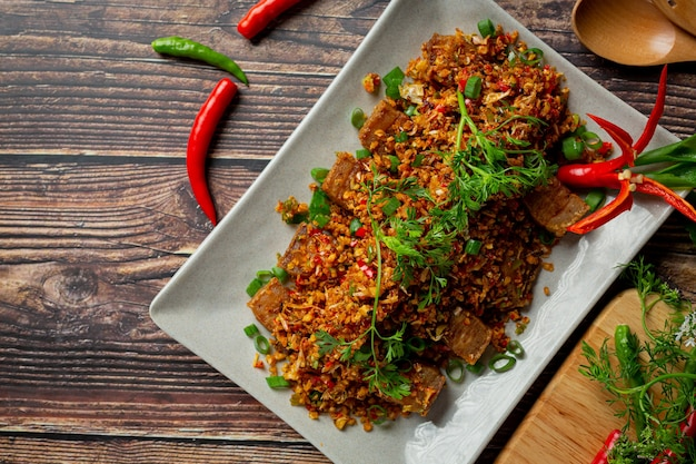 Gebakken varkensvlees met gedroogde chili en zout op donkere achtergrond