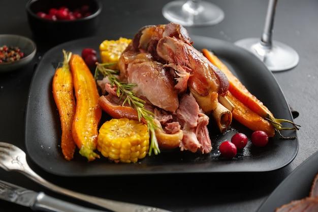 Gebakken varkensvlees met groenten en kruiden op plaat. detailopname