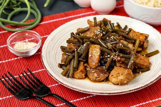 Gebakken varkensvlees met knoflookpijlen en sojasaus, bestrooid met sesamzaadjes in een bord