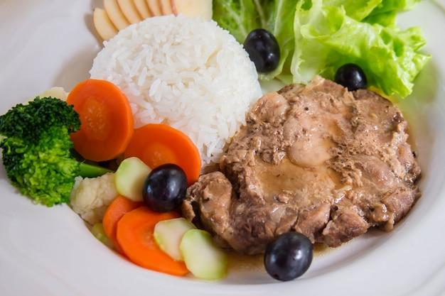 Gebakken varkensvlees op een witte plaat. decoreer met kleurrijke groenten en fruit.