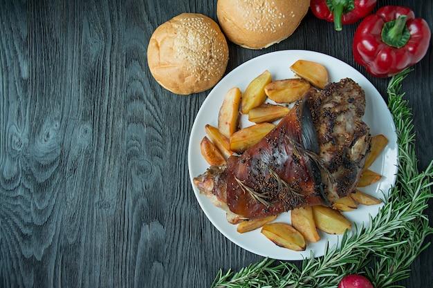 Gebakken varkensvlees schacht met aardappelen geserveerd op een witte plaat gebakken varkensvlees. donker houten. uitzicht van boven.