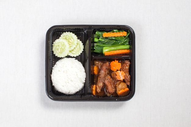 Gebakken varkensvleesrijst die in een zwarte plastic doos wordt gedaan, op een wit tafelkleed, voedseldoos, thais voedsel wordt gezet.