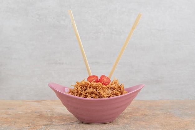 Gebakken vermicelli met tomaat in roze kom met eetstokjes. hoge kwaliteit foto