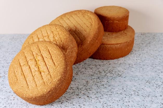 Gebakken verschillende maten biscuit op tafel voor het maken van cake.