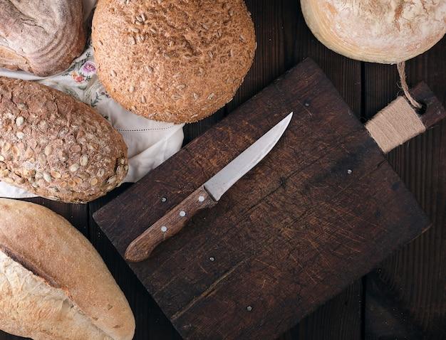 Gebakken verschillende soorten brood op een beige keuken handdoek, houten achtergrond