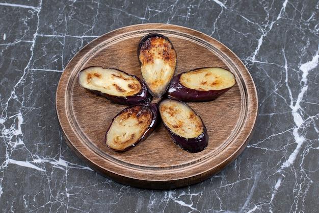 Gebakken verse aubergine (aubergine) plakjes op een houten bord.