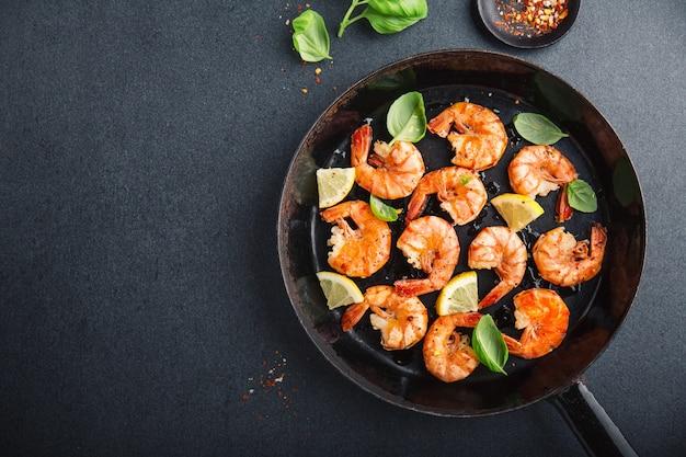 Gebakken verse garnalen met specerijen op zwarte pan