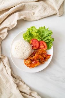 Gebakken vis bekroond door 3 smaken chilisaus met rijst op een witte plaat
