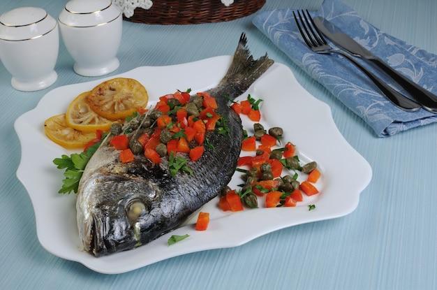 Gebakken vis (dorado) gedecoreerd met plakjes paprika met kappertjes