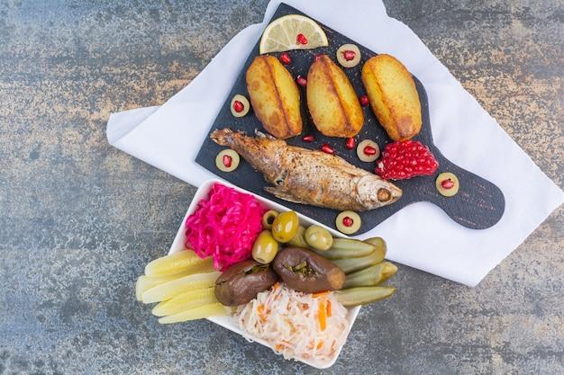 Gebakken vis en aardappel op een snijplank naast een kom met geconserveerde groenten.