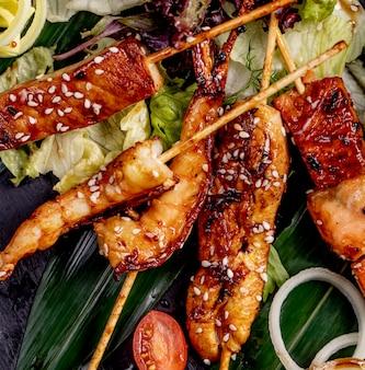 Gebakken vis en garnalen op stokjes geserveerd met sla tomaten en uien