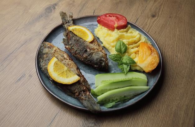 Gebakken vis en groenten op een plaat op een houten tafel