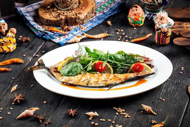 Gebakken vis gevuld met verse groenten en citroenen op de zwarte houten