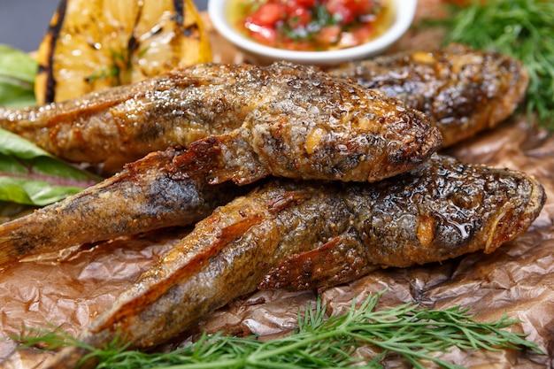 Gebakken vis grondel met saus op een houten bord