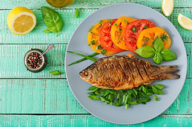 Gebakken vis karper en verse groente salade op houten tafel. plat liggen. bovenaanzicht