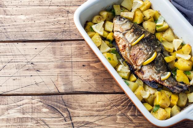 Gebakken vis karper met aardappelen in een keramische pan. rustieke stijl. copyspace