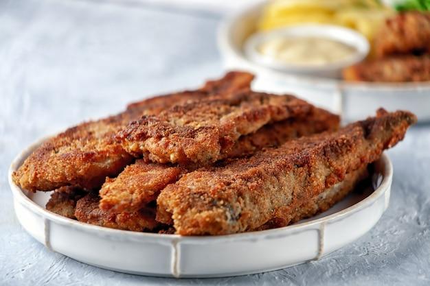 Gebakken vis met gebakken aardappelen, doperwtjes en citroen